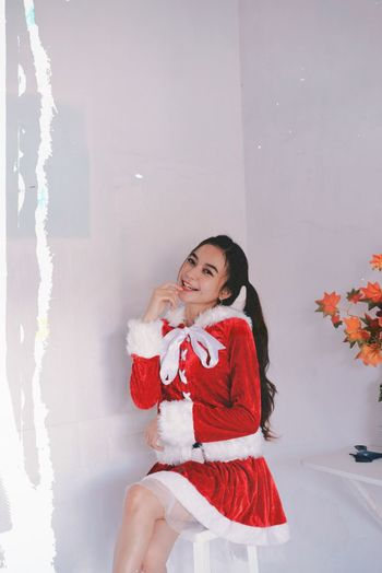 Smiling young woman wearing santa costume sitting against wall
