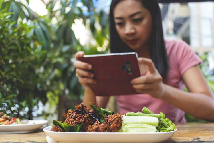 Midsection of woman holding mobile phone while sitting on table