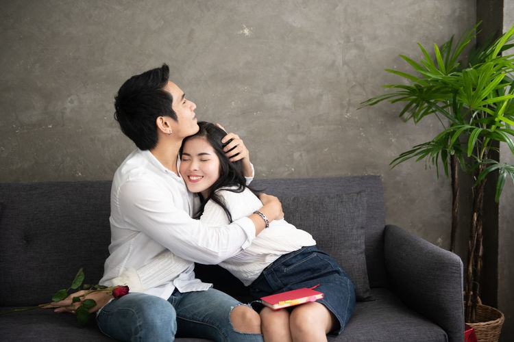 Picture of young man surprising woman with flowers Young Adult Togetherness Emotion Women Two People Young Women Positive Emotion Happiness Lifestyles Sofa Love Smiling Indoors  Leisure Activity Young Men Bonding Sitting Couple - Relationship Girlfriend Living Room Boyfriend Arm Around Love Romantic Valentine's Day