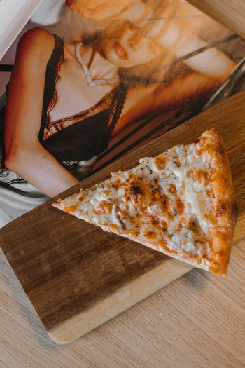 High angle view of hand holding pizza on table