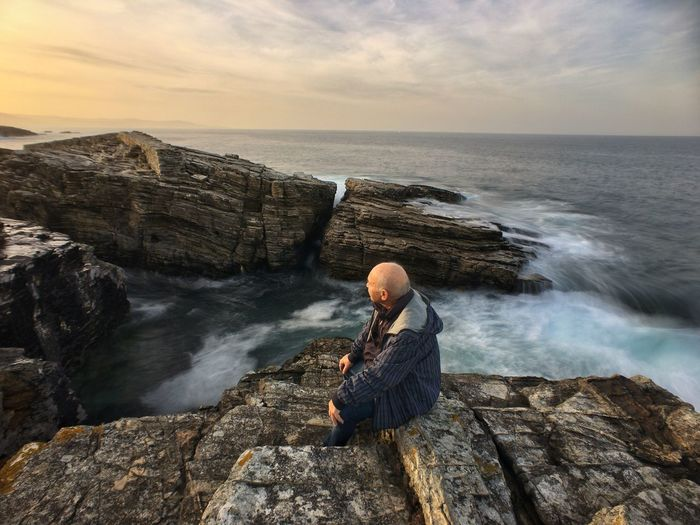 Senior man sitting on rock by sea against sky during sunset