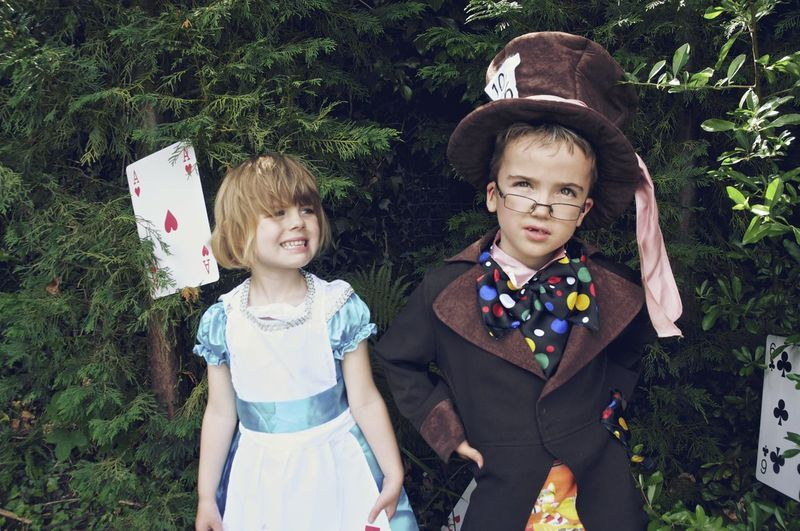 Boy And Girl In Costumes Standing Against Trees