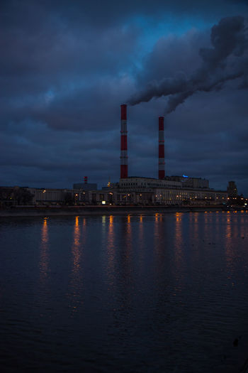 Smoke emitting from factory by river at dusk