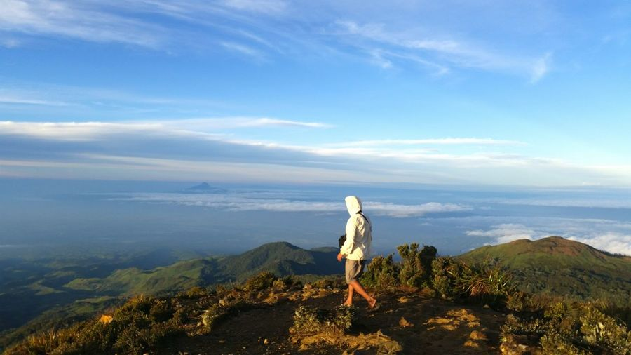 Rear view of man hiking on mount apo against sky