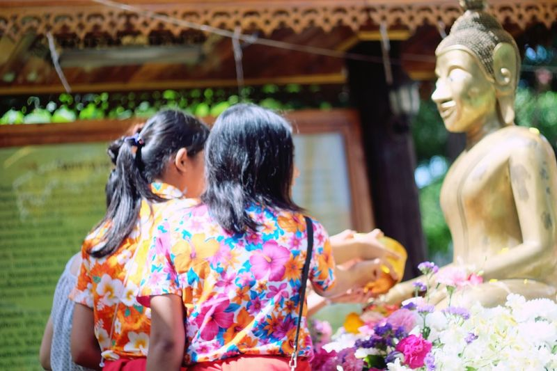 Women offering to bronze buddha statue during songkran festival on sunny day