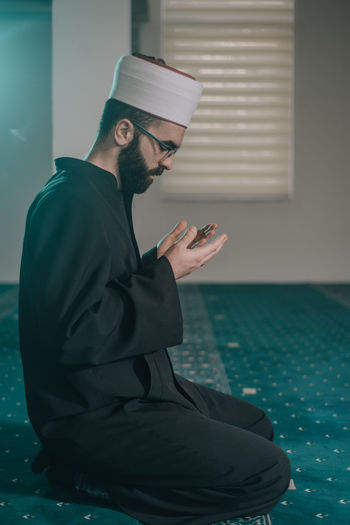 Side view of man sitting in mosque