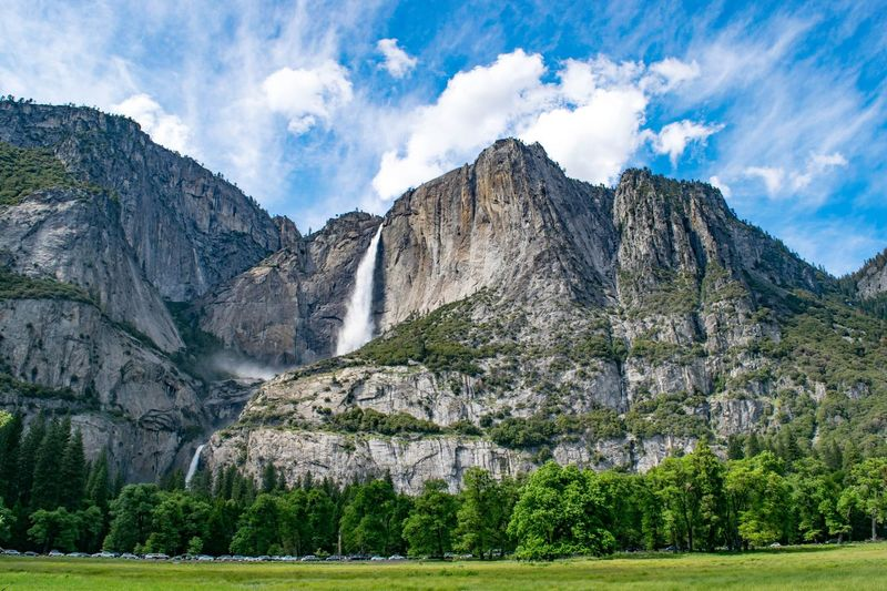 Scenic View Of Waterfall Flowing From Rocky Mountains Against Sky