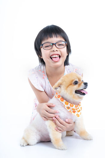 Isolated portrait Asian little girl holding Pomeranian dog with care on white background. Studio shot of girl and puppy Domestic Animals Domestic Real People One Animal Mammal One Person Pets Women Smiling Front View White Background Casual Clothing Lifestyles Emotion Vertebrate Leisure Activity Hairstyle Pet Owner Indoors  Studio Shot Tounge Out  Love Hug Bright Cheerful Funny Joyful