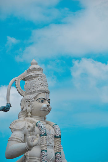 Low angle view of hanuman statue against blue sky