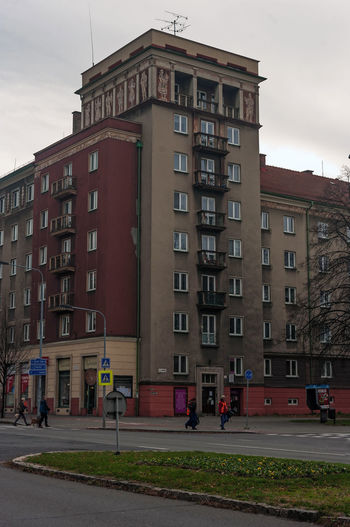 Building by road against sky in city