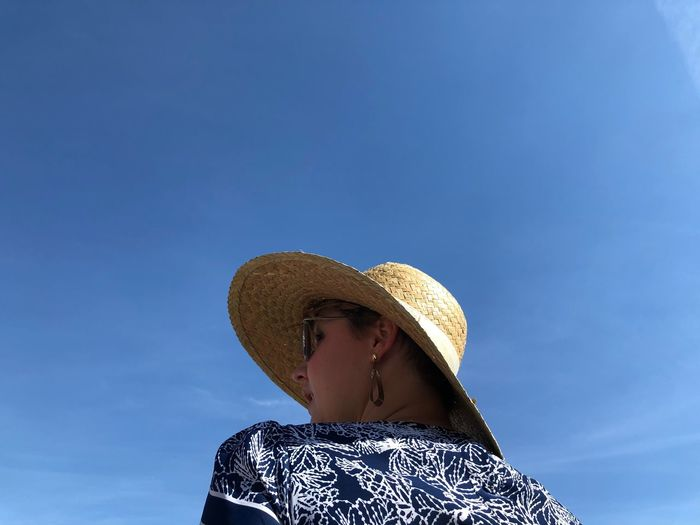 Low angle view of woman wearing hat against blue sky