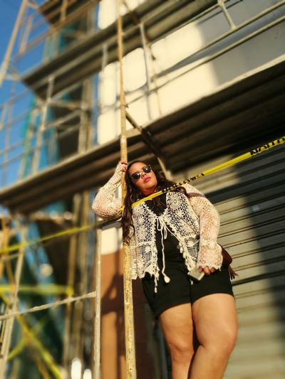 Low angle view of woman standing by scaffolding and cordon tape against built structure