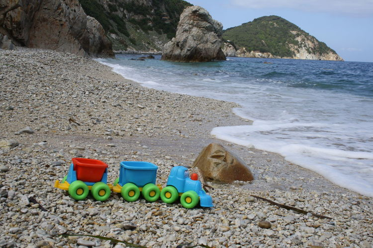Multi colored toy on rock by sea shore