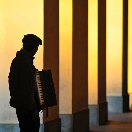 Silhouette of a solitary accordion player street musician against a backdrop of yellow columns.