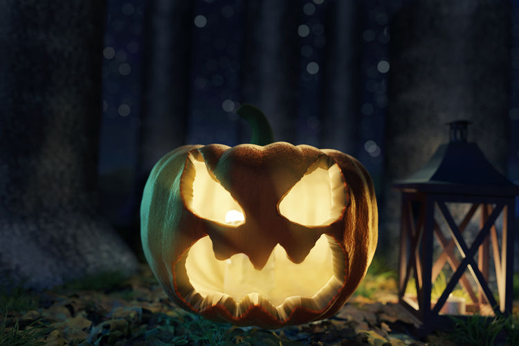 Close-up view of illuminated pumpkin against stone wall during halloween