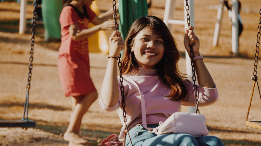 Portrait of happy girl sitting on swing at park