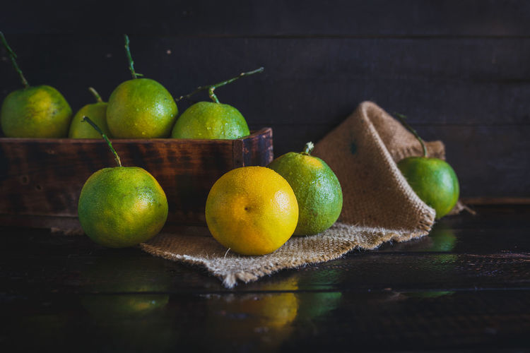 Oranges Food, Natural, Dark Background, Healthy, Fresh, Fruit, Rustic, Vietnamese Fruit, Asia, Vietnam, Tropical, Diet, Farm, Plant, Nutrition, Orange, Green, Green Orange, Burlap, Cutting Board, Dark Wood, Box, Yellow