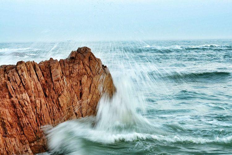 Wave Splashing On Rock Formation In Sea Against Sky