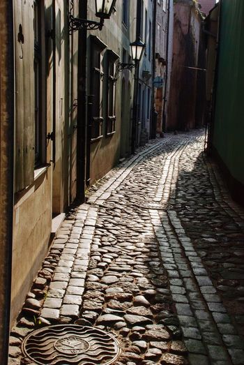 Old alley in Riga, Latvia Old Town Alley Latvia Riga Architecture Building Exterior Built Structure The Way Forward Direction Cobblestone Footpath No People City Street Building Shadow Day Sunlight Pattern Residential District Paving Stone Diminishing Perspective Outdoors