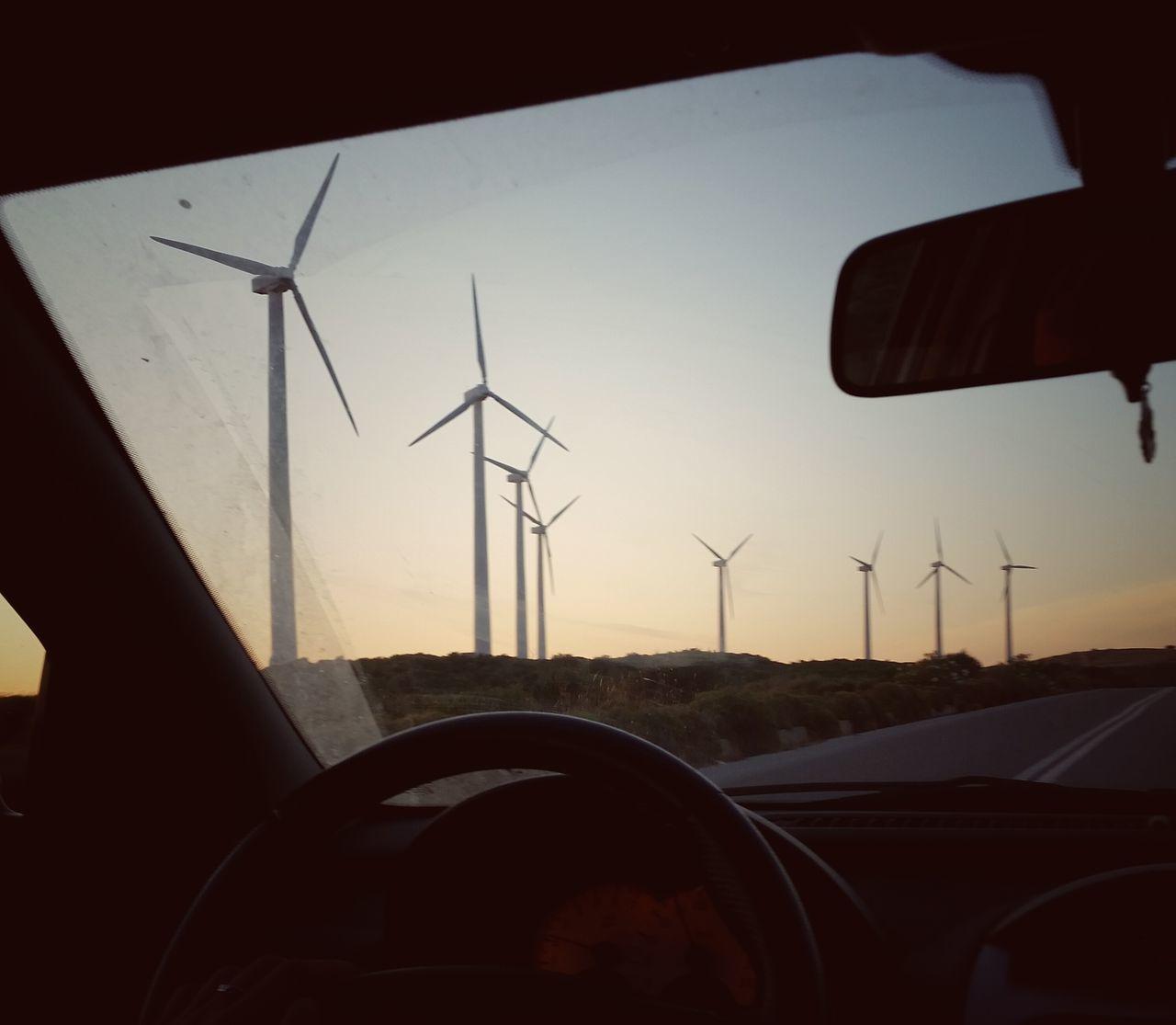Windmills Seen Through Car Windshield During Sunset