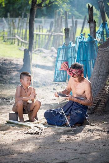 Shirtless Boy Sitting By Craftsperson On Ground