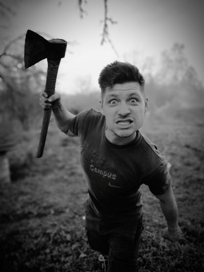 Portrait Of Angry Man With Axe Standing On Field