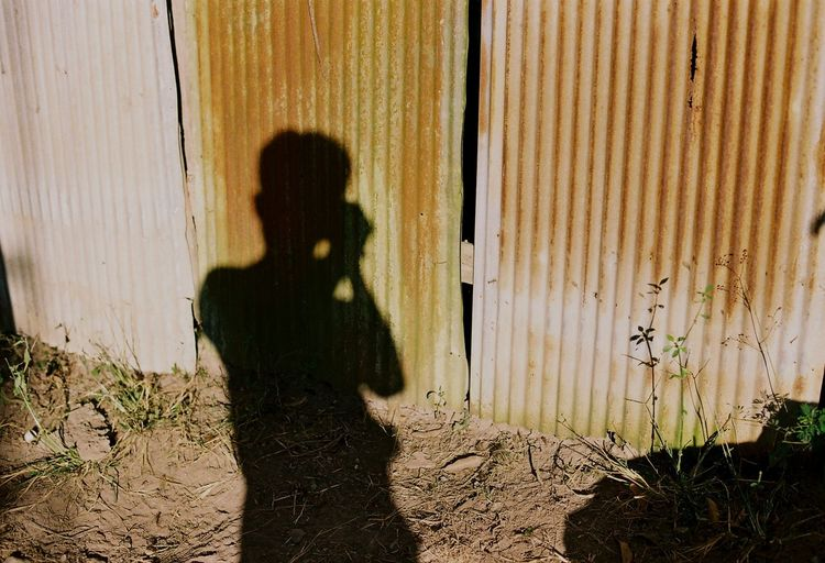 Shadow Of Man Photographing Corrugated Iron Fence