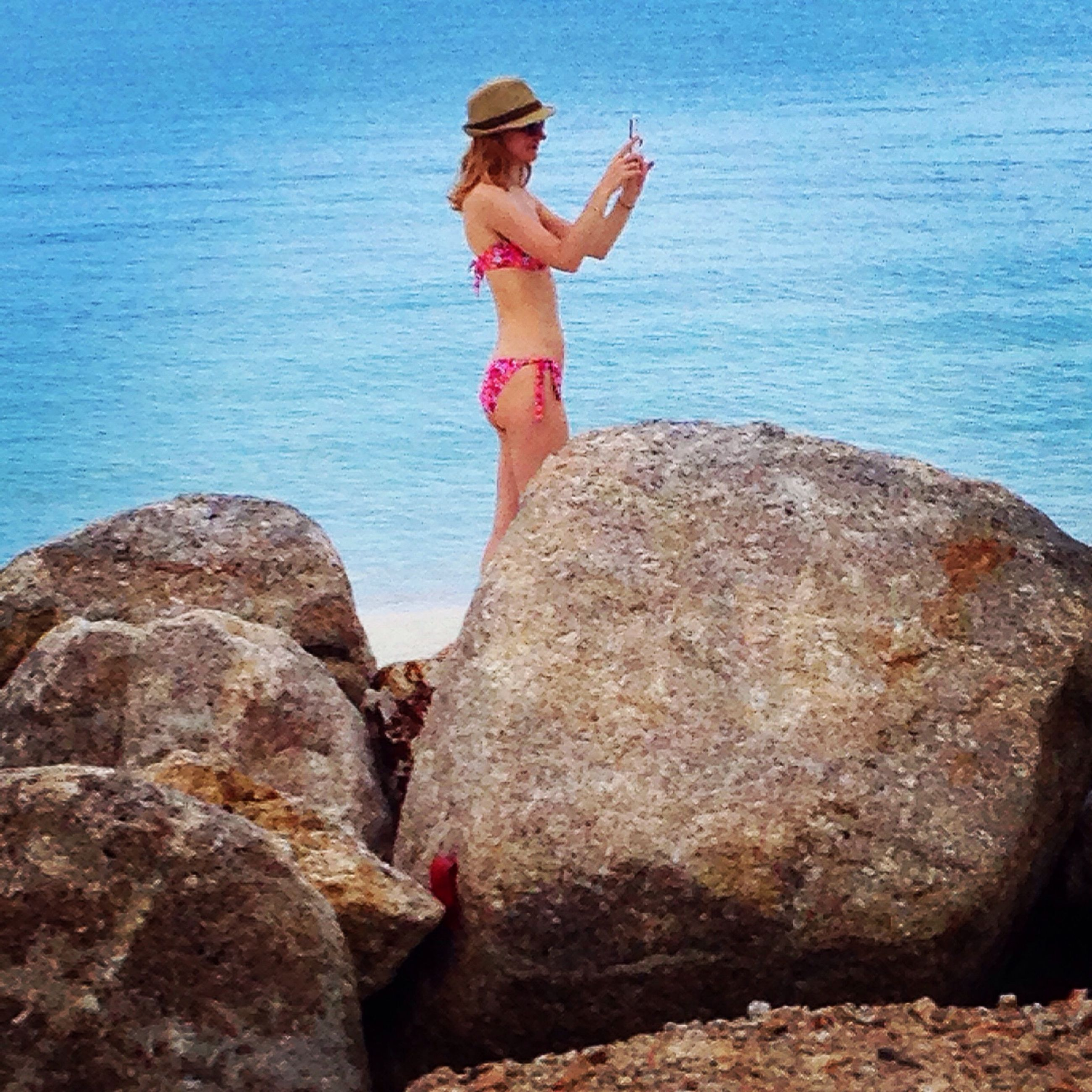 water, sea, rock - object, lifestyles, leisure activity, standing, full length, rock formation, blue, vacations, rock, person, tranquility, nature, scenics, beauty in nature, day, shore
