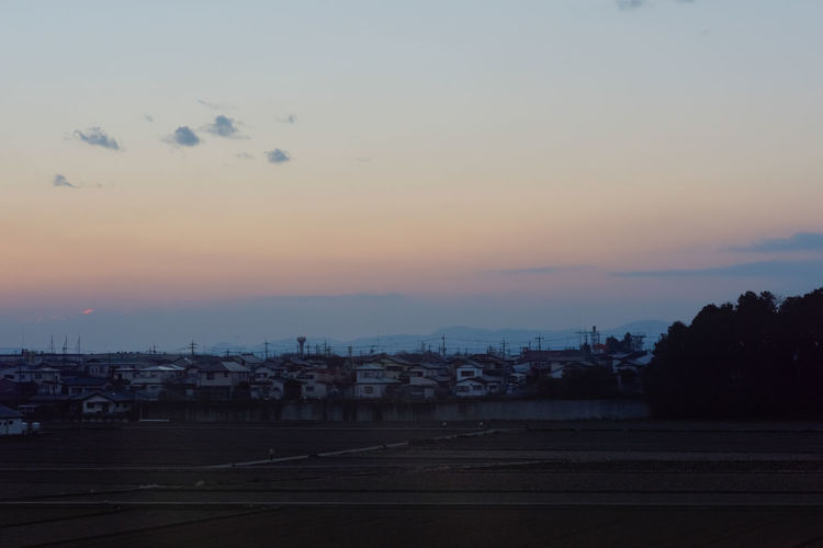 Silhouette of city against cloudy sky