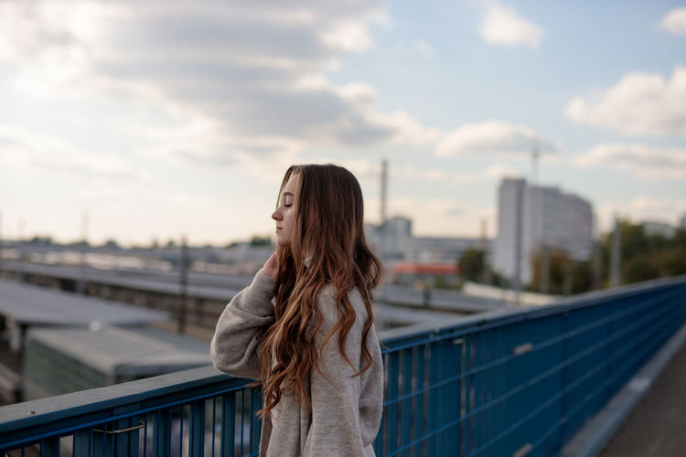 Young woman with eyes closed standing by railing against sky in city