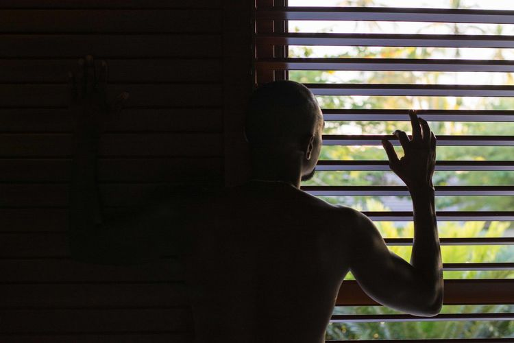 Rear view of man looking through window