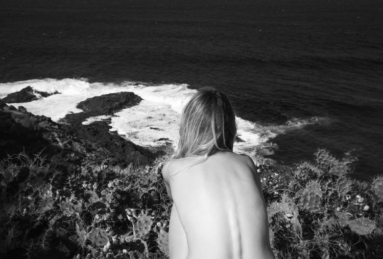 Rear view of shirtless woman looking at sea