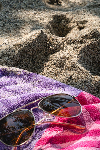 High angle view of sunglasses on sand at beach
