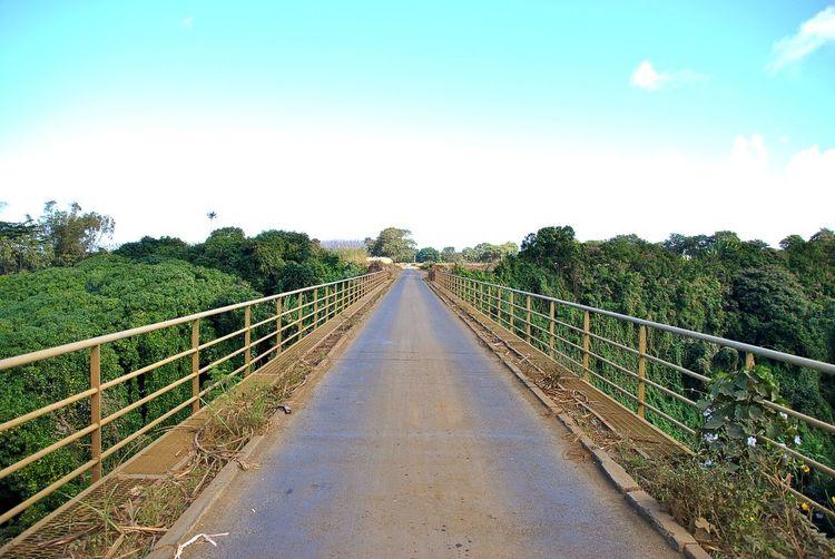 Footbridge over road against sky