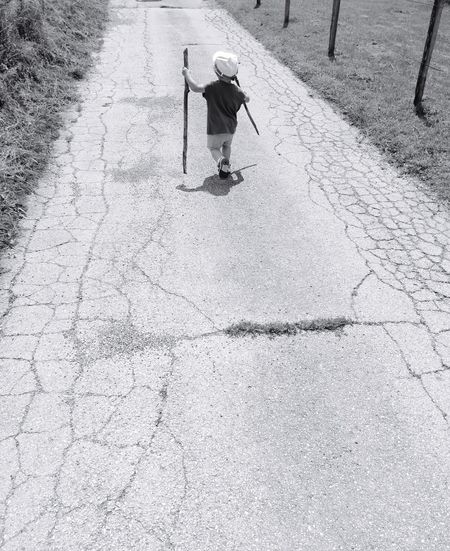 Rear view full length of boy holding sticks on road