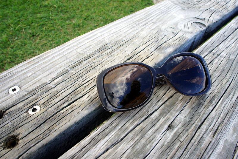 Close-up of sunglasses on wood