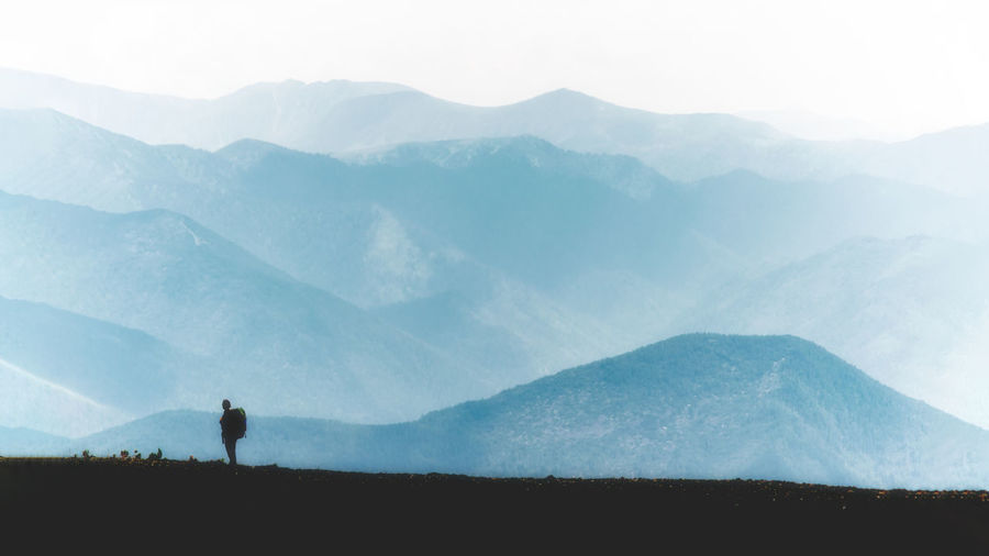 One woman in the mountain ridge with backpack with blue colours