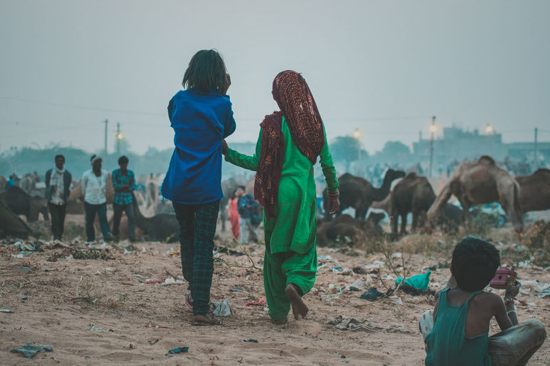 Real People Land Domestic Animals Domestic Pets Mammal Men Group Of People Nature Women Lifestyles Livestock Group Of Animals Vertebrate Incidental People Field Leisure Activity Rear View Outdoors Pushkar India Rajasthan