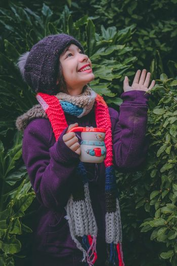 Thoughtful girl smiling while having drink in cup against plants