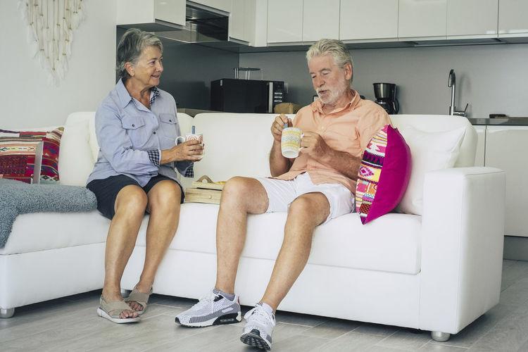 Senior couple having drinks on sofa at home