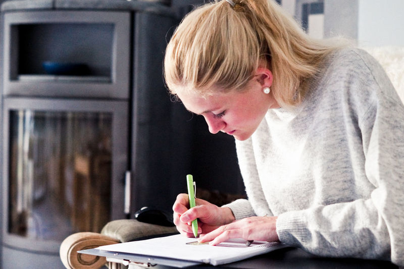 Young Woman Writing On Paper At Home