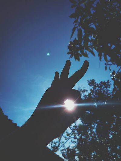 Low angle view of person hand against bright sun