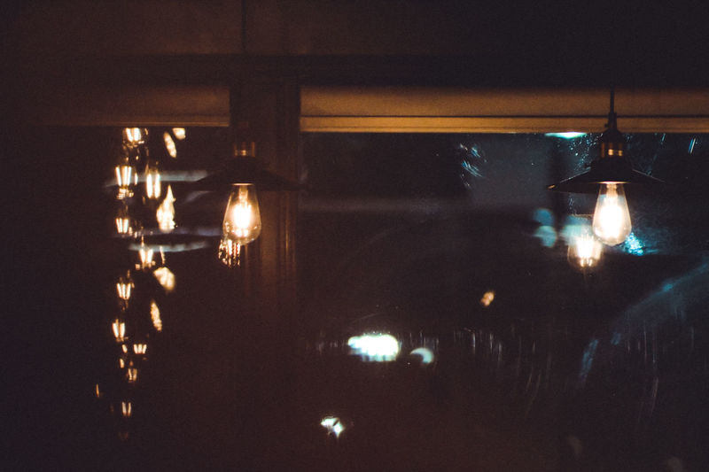Illuminated lights hanging from ceiling in restaurant