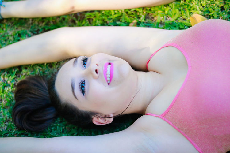 High Angle View Of Young Woman Lying Down On Field
