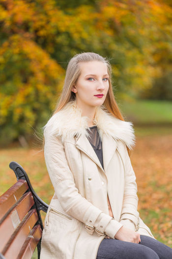 Portrait of girl sitting on bench in park