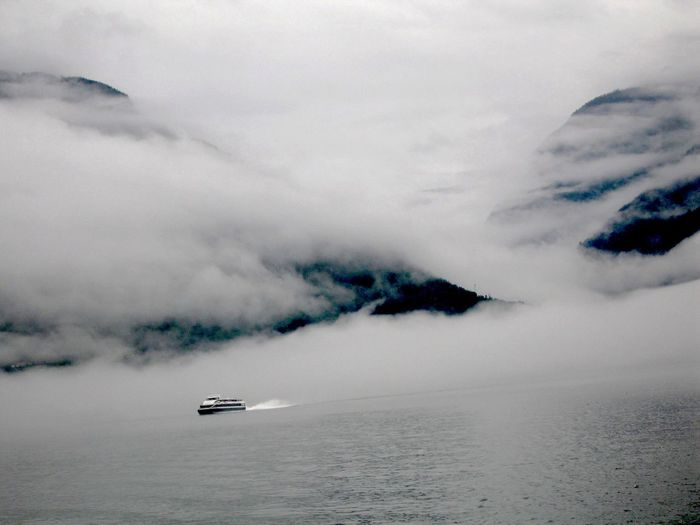 Cruise ship sailing by sea against mountains covered with clouds
