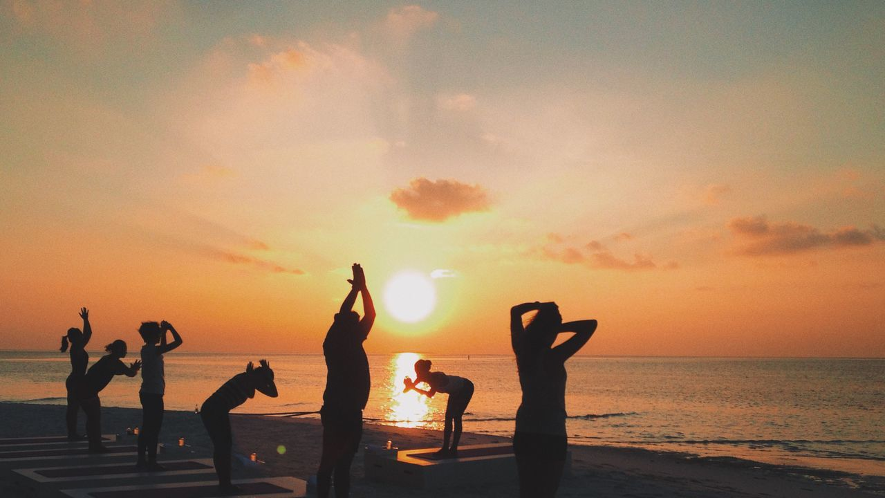 Silhouette women exercising on beach by sea against sky during sunset