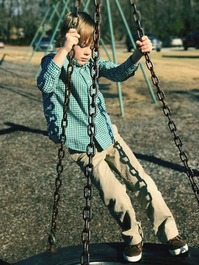 Full length of boy playing on swing in playground