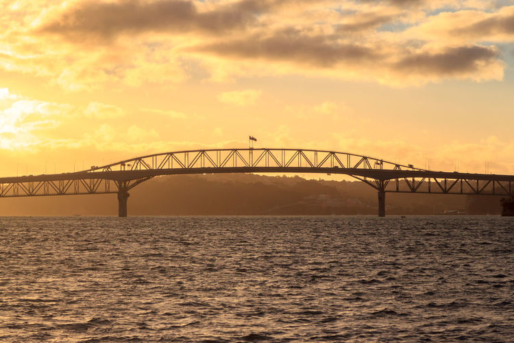 Auckland Harbour Bridge at sunset Auckland Harbour Bridge Architecture Beauty In Nature Bridge Bridge - Man Made Structure Built Structure Cloud - Sky Connection Engineering Nature Orange Color Outdoors Scenics - Nature Sea Sky Sunset Transportation Water Waterfront