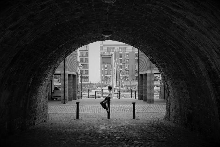 Boy Sitting On Bollard Seen Through Arch